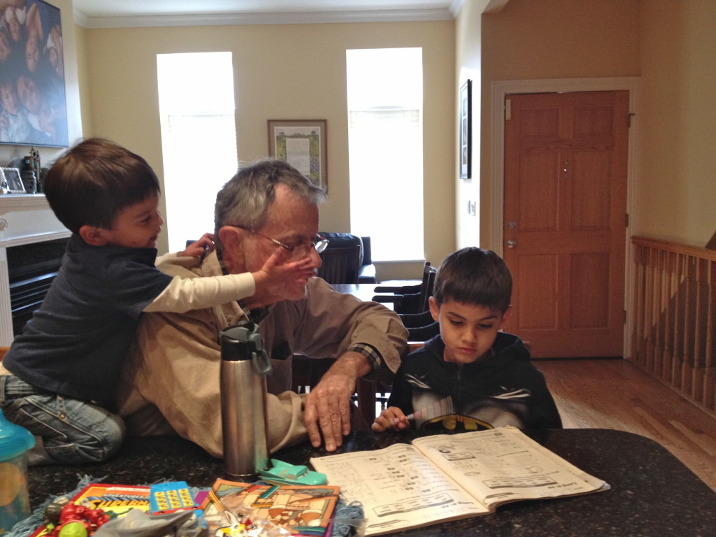 Grandpa helping Jack with his homework while Aaron tries to steal his glasses.