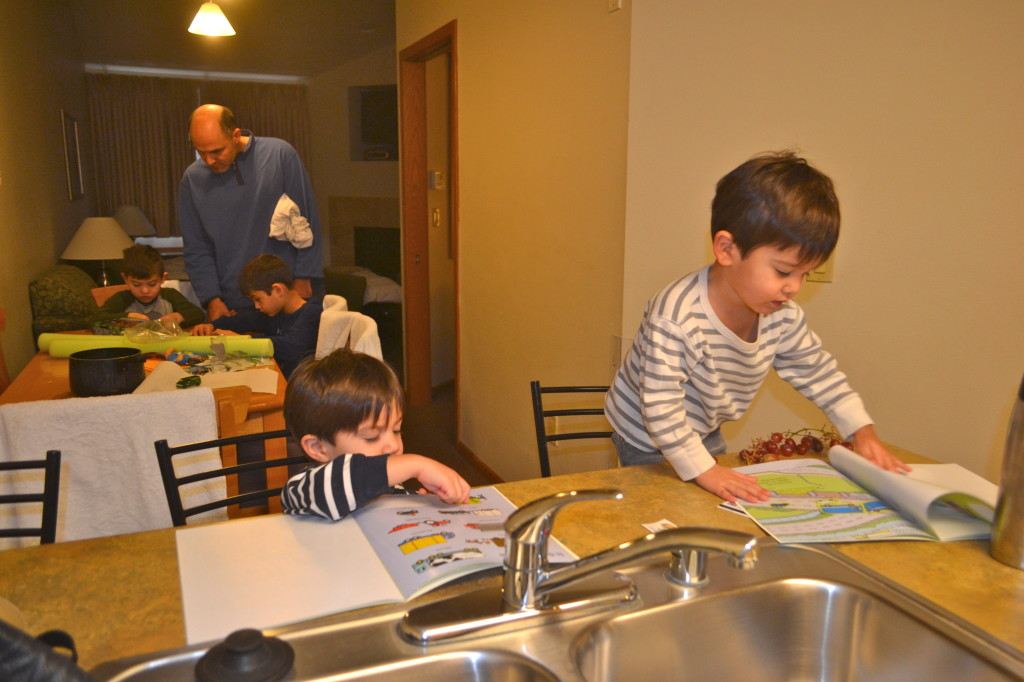 Twins playing with their new sticker books from Hanukkah while the older boys do a new puzzle with Adam.